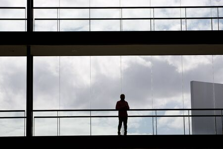 Silhouette view of a businessman in a modern office building interior with panoramic windows. photo