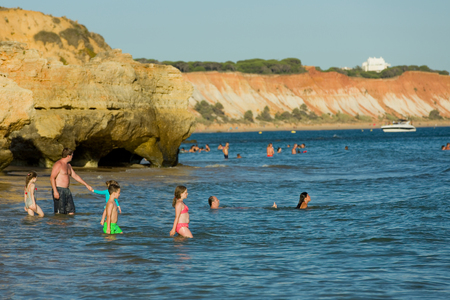 turism: People at the famous beach of Olhos de Agua in Albufeira. This beach is a part of famous tourist region of Algarve. Editorial