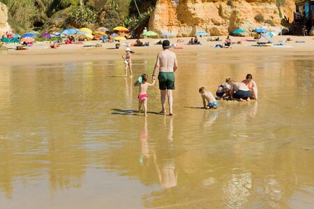 region of algarve: People at the famous beach of Olhos de Agua in Albufeira. This beach is a part of famous tourist region of Algarve. Editorial