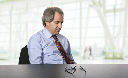 sad  mature business man on a desk, at the office photo