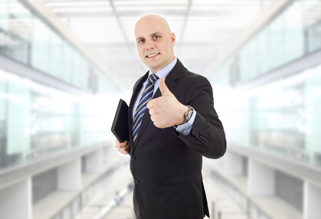 proud businessman with a tablet pc going thumb up, at the office photo