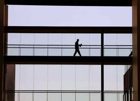 Silhouette view of young businessman in a modern office building interior with panoramic windows. photo