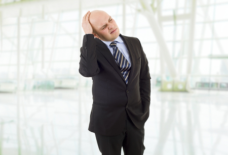 hardworker: Businessman in a suit gestures with a headache at the office