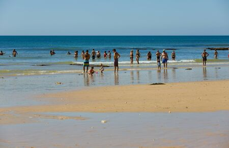 turism: ALBUFEIRA, PORTUGAL - AUGUST 20, 2016: People at the famous beach of Olhos de Agua in Albufeira. This beach is a part of famous tourist region of Algarve.