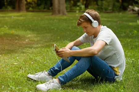 young man relaxing with a tablet pc listening music with headphones at the park, outdoor Stock Photo
