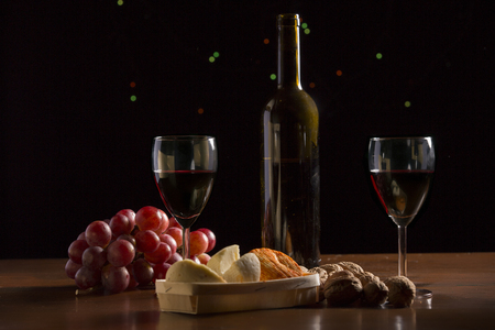 Composition with wine, cheese, nuts and grape on wooden table, on black background Stock Photo