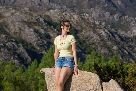 Young happy woman sitting on the rock mountain, relaxing and enjoying the valley view at Geres, Portuguese National Park