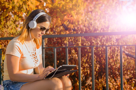 casual woman working with a tablet pc, with headphones, outdoor Stock Photo