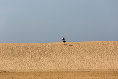 Man at the dunes of the famous beach of Praia da Bordeira. This beach is a part of famous tourist region of Algarve. Stock Photo