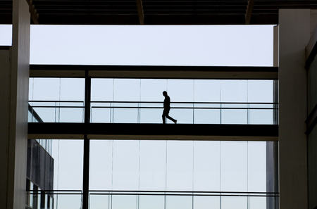 Silhouette view of young businessman in a modern office building interior with panoramic windows. Stock Photo