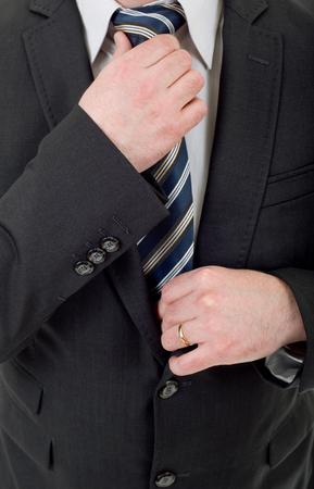 businessman in black suit adjusting tie