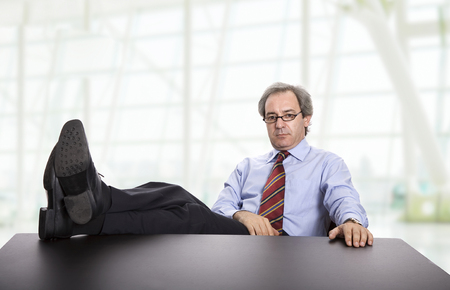 mature business man on a desk, at the office Stock Photo