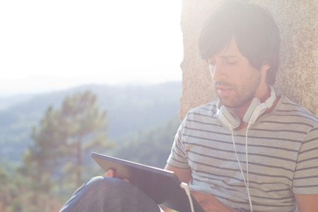 young man working with a tablet pc listening music with headphones, outdoor Stock Photo
