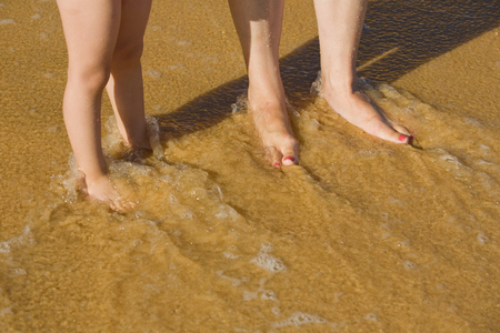 legs on the beach, mother and child at the wet sand