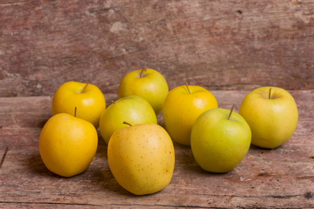 yellow apples on a old wooden background