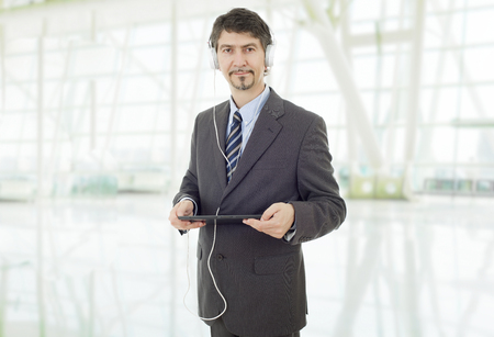 businessman with tablet pc and headphones, at the office