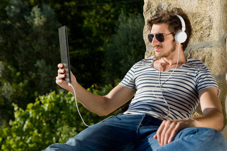 young man listening music with headphones, outdoor