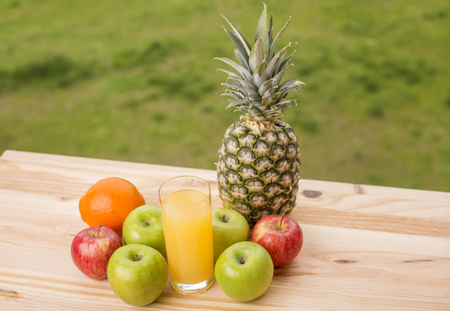 glass of orange juice and lots of fruits on wooden table outdoor Stock Photo