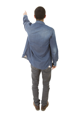 young casual man full body pointing in a white background