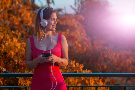 beautiful casual woman enjoying music at the sunset, with headphones, outdoor Stock Photo