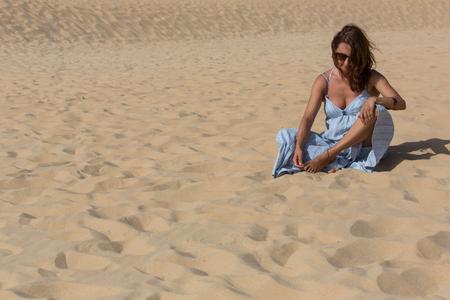 woman at the sand dunes of Praia da Bordeira, Algarve, the south of Portugal