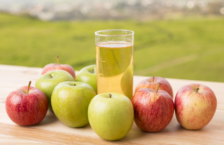 apples and apple juice on a wooden table, outdoor