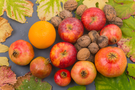 Autumn fruits still life among leaves on wooden table