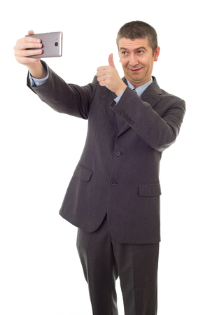 businessman in suit and tie taking selfie photo with mobile phone camera posing happy and successful isolated on white background Stockfoto
