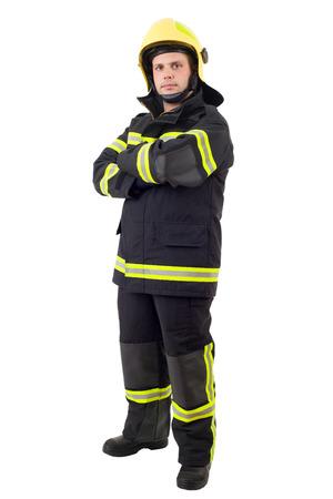 Poważny strażak pozuje ze skrzyżowanymi rękami. Pełna długość studio strzał na białym tle. Zdjęcie Seryjne