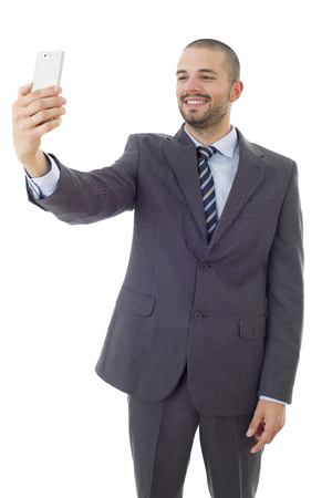 businessman in suit and tie taking selfie photo with mobile phone camera posing happy and successful isolated on white background Stock Photo