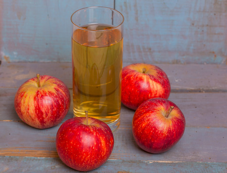 Glass of apple juice and a red apples on a blue old wooden background