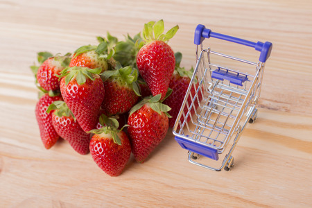 strawberries and a shopping cart on gardens table, outdoor picture