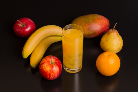 variety of fruits and orange juice on a black background, studio picture