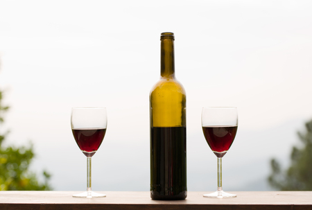 wine bottle and glass on wooden table, outdoor Stock Photo