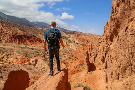Issyk-Kul, Kyrgyzstan: Hiker on the red sandstone rock formations Seven bulls and Broken heart, Jeti Oguz canyon in Kyrgyzstan, Issyk-Kul region, Central Asia 에디토리얼