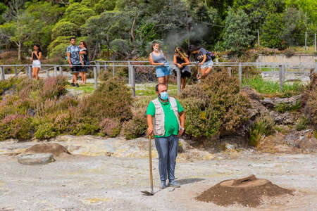 Furnas, Sao Miguel, Azores island, Portugal: people watch as worker take out Cozido, an Azores meal cooked in the ground near thermal vents at Fumarolas da Lagoa das Furnas in Azores, Portugal