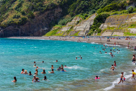 Ribeira Quente, Sao Miguel island, Azores, Portugal - August 15, 2020: People swimming in the sea and relaxing on a nice sandy beach Praia do Fogo by the town Ribeira Quente. Popular with both local people and tourists. 에디토리얼