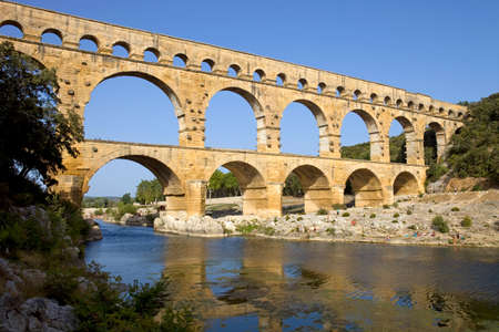 NIMES, FRANCE: People near the famous landmark ancient old double arches of Roman aqueduct of Pont du Gard, Nimes, France
