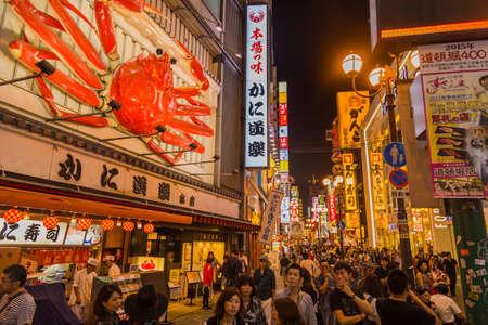 Osaka, Japan: Tourist walking in a shopping street called Dotonbori Street. Giant moving crab on restaurant in Dotonbori Osaka, Namba Dotonbori area at night, Osaka, Japan