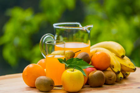 orange juice and fruits on a table, outdoor