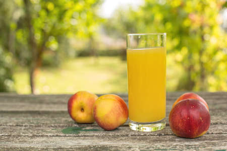 peaches and peach juice on a wooden table, outdoor Stok Fotoğraf