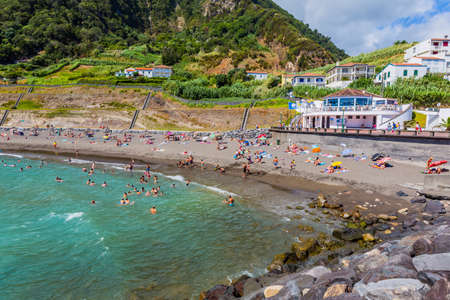 Ribeira Quente, Sao Miguel island, Azores, Portugal - August 15, 2020: People swimming in the sea and relaxing on a nice sandy beach Praia do Fogo by the town Ribeira Quente. Popular with both local people and tourists. Stok Fotoğraf