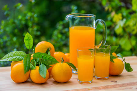 orange juice and oranges on table, outdoor Stock Photo