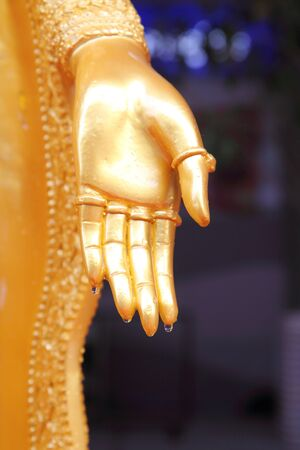 spiritual architecture: water drop at the hand of Buddha statue
