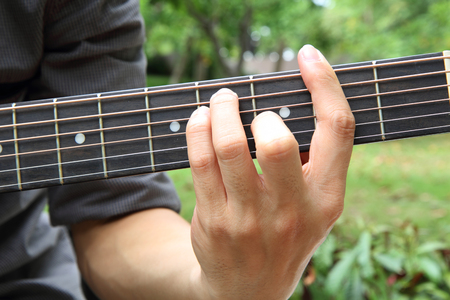 chord: playing guitar chord F  playing guitar in the park Stock Photo
