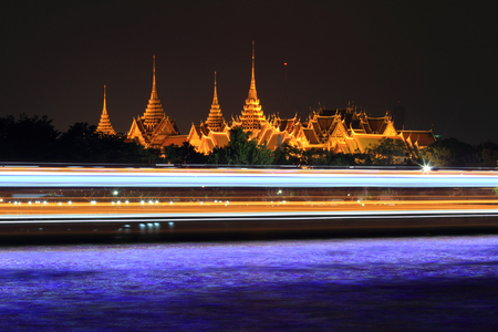 the emerald city: Bangkok, Thailand - December 31, 2015: Wat Phra Kaew and moving light of boat passing in the river Editorial