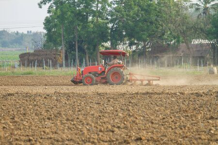 plough machine: tractors plow the farm in local country