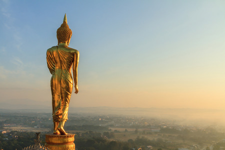 december sunrise: Nan,Thailand - December 21, 2014 : behind of golden buddha statue in sunrise time Editorial