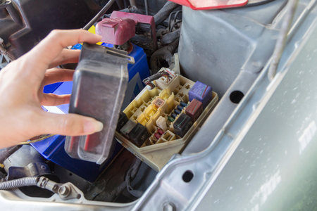 car fuse: The man opening fuse box of old car