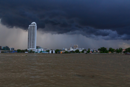 Dark cloud storm in the city near the river  Rain coming on the sky in the city view Stock Photo